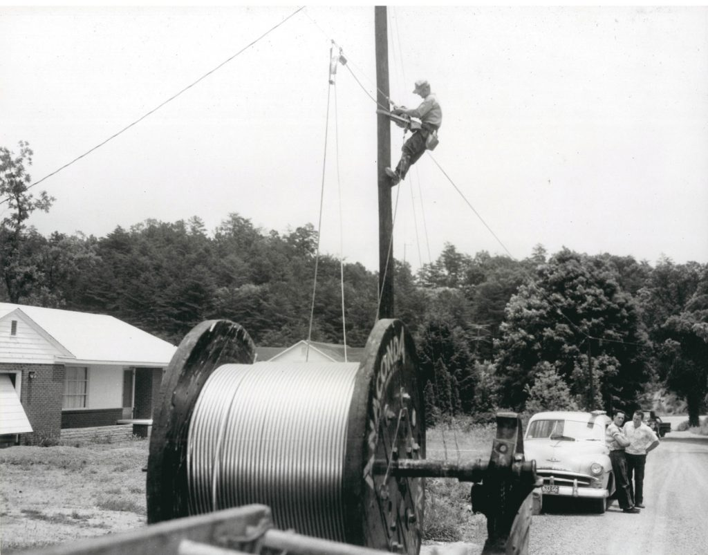 1950's era nostalgic photo of lineman on utility pole running cable as residents watch in background.